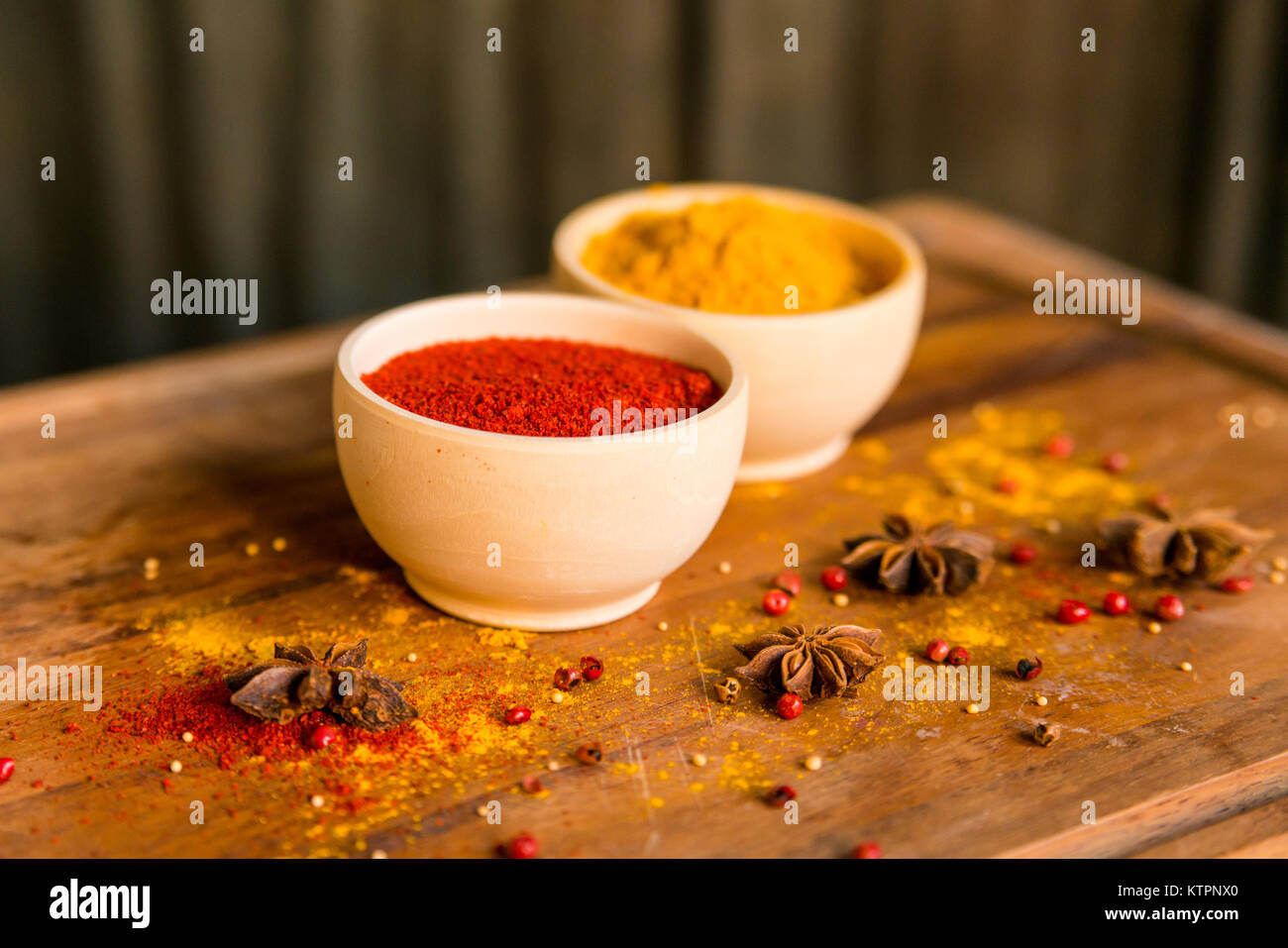 Close up two bowls filled with red paprika and yellow turmeric powder on dark wooden table covered with anise - Stock Image