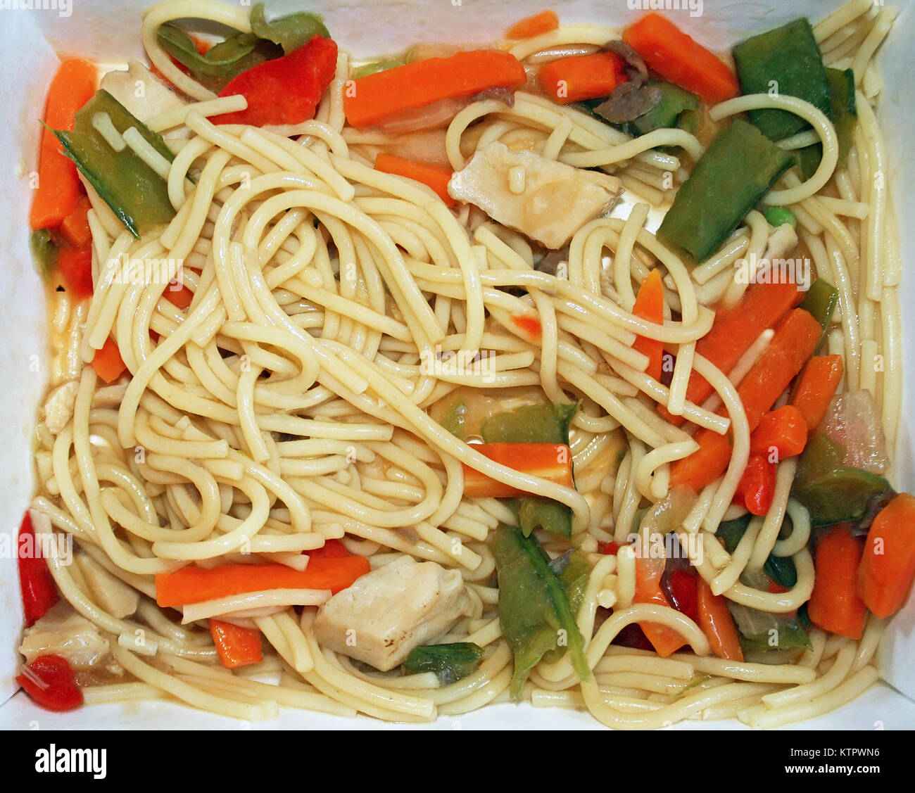 Cardboard container of noodles and vegetables that has been microwaved Stock Photo
