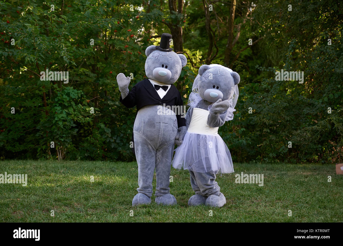 Couple dressed as teddy bear bride and groom standing in park Stock Photo