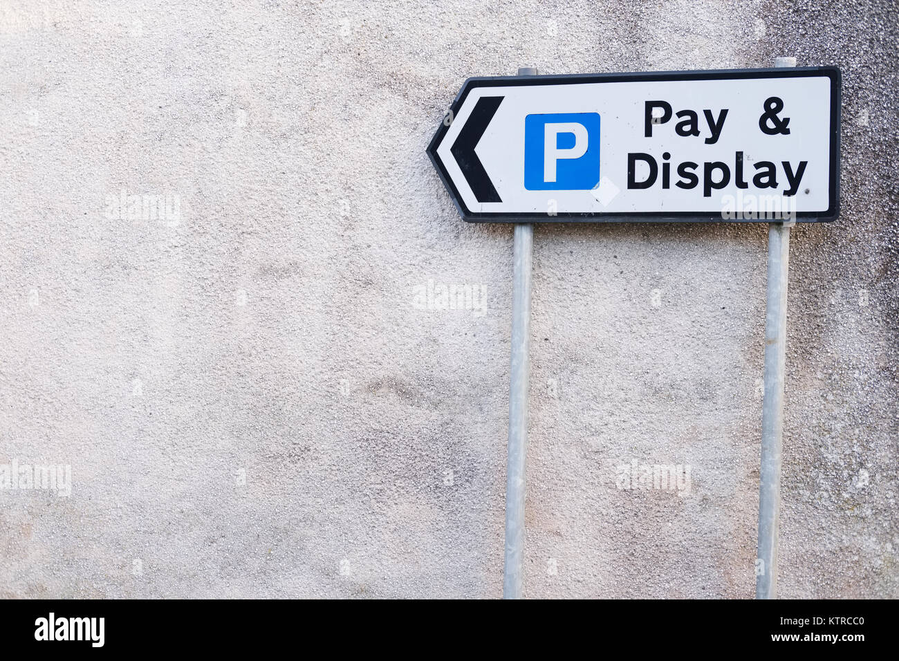 Pay and Display Sign on Wall with Directions given by Arrow - Stock Image