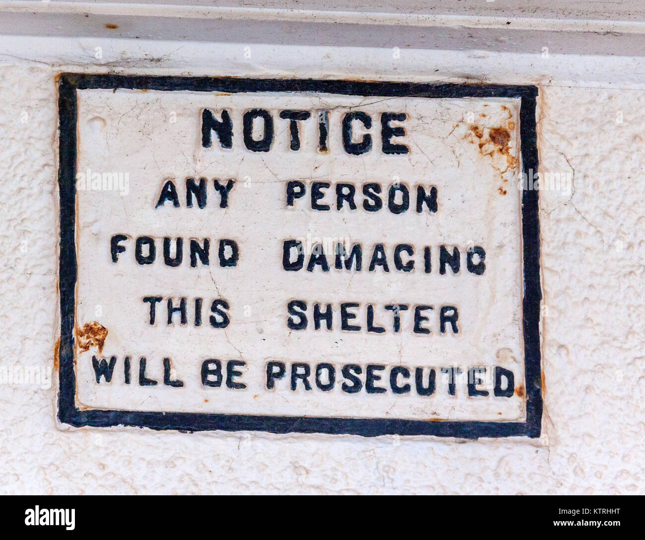Old rusty warning sign - Notice any person found damaging this shelter will be prosecuted. - Stock Image