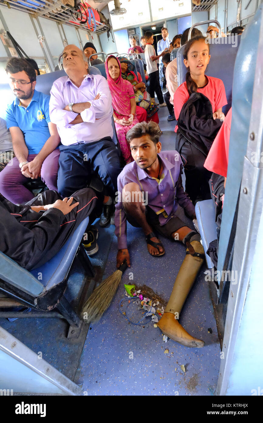 Disabled man cleaning the floor of a railway carriage in return for offerings, India - Stock Image