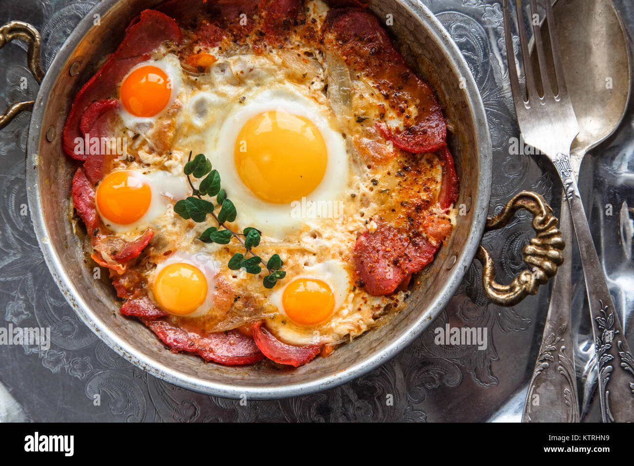 Closeup of Turkish pastirmali and fried egg in a copper pan on wooden table - Stock Image