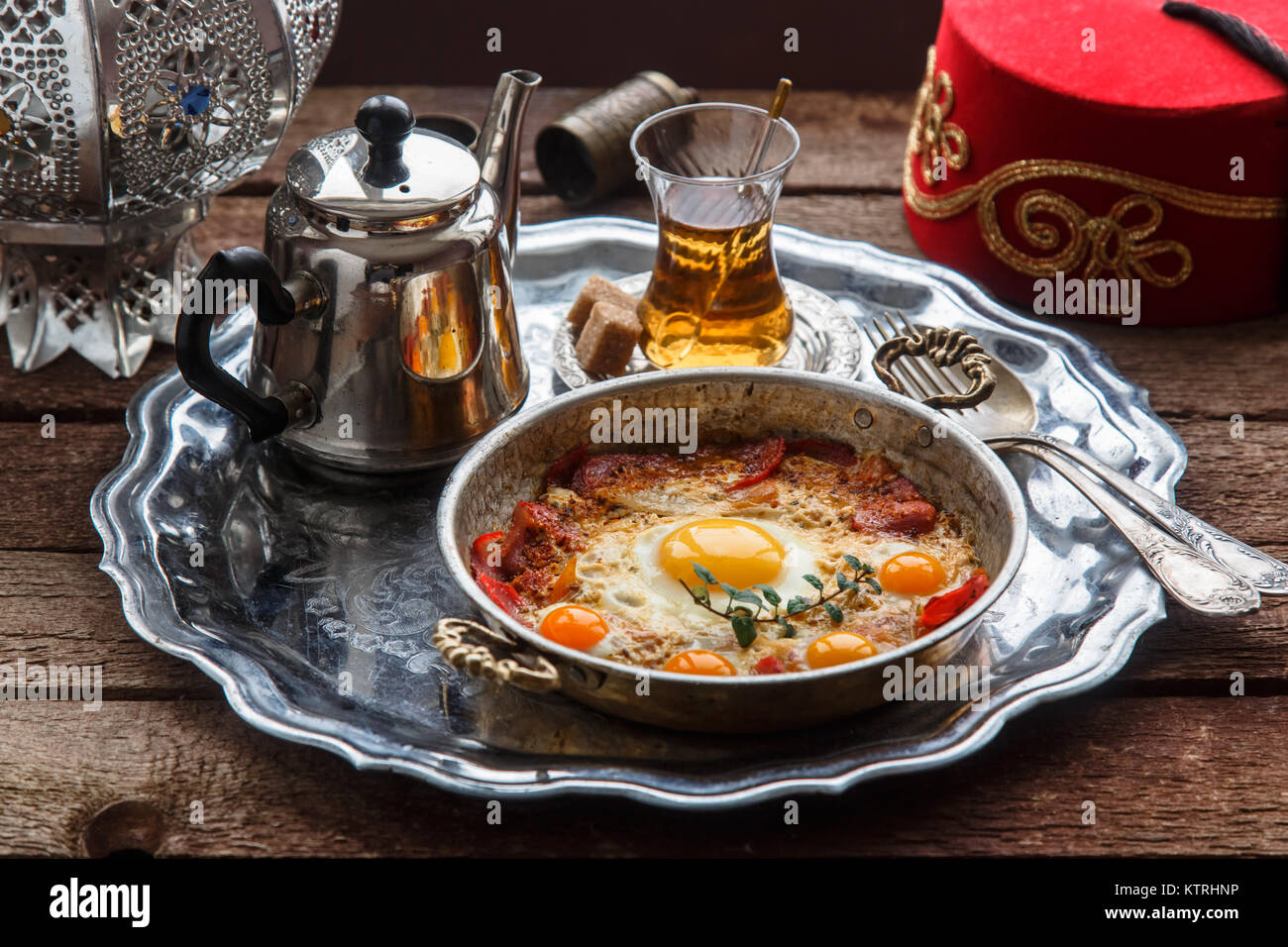 Fried egg with cured meat, traditional turkish breakfast, served in metal dishware, rustic Stock Photo