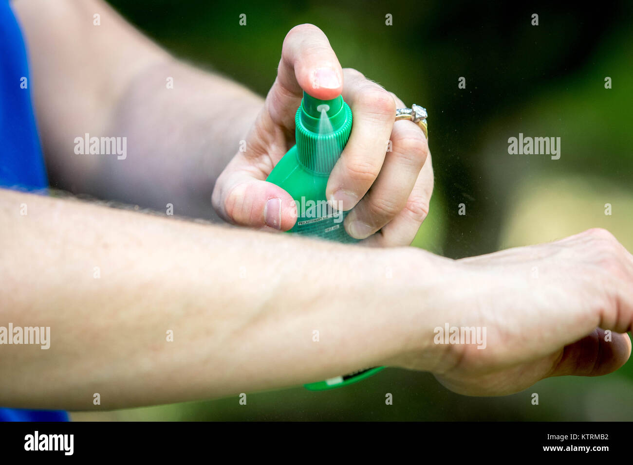 Woman sprays herself with mosquito repellent - Stock Image