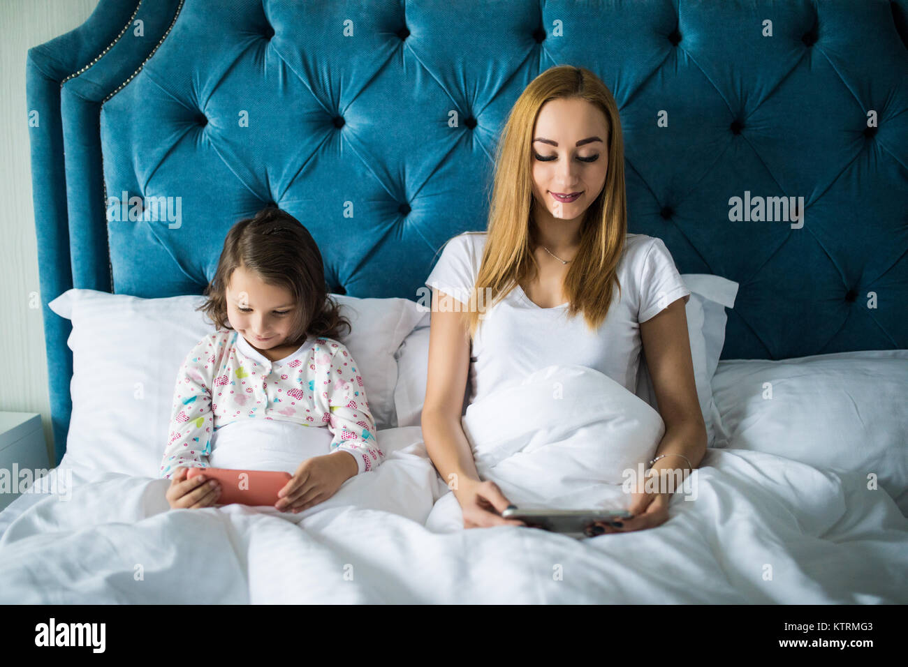 Smiling mom and daughter relaxing on the bed - Stock Image
