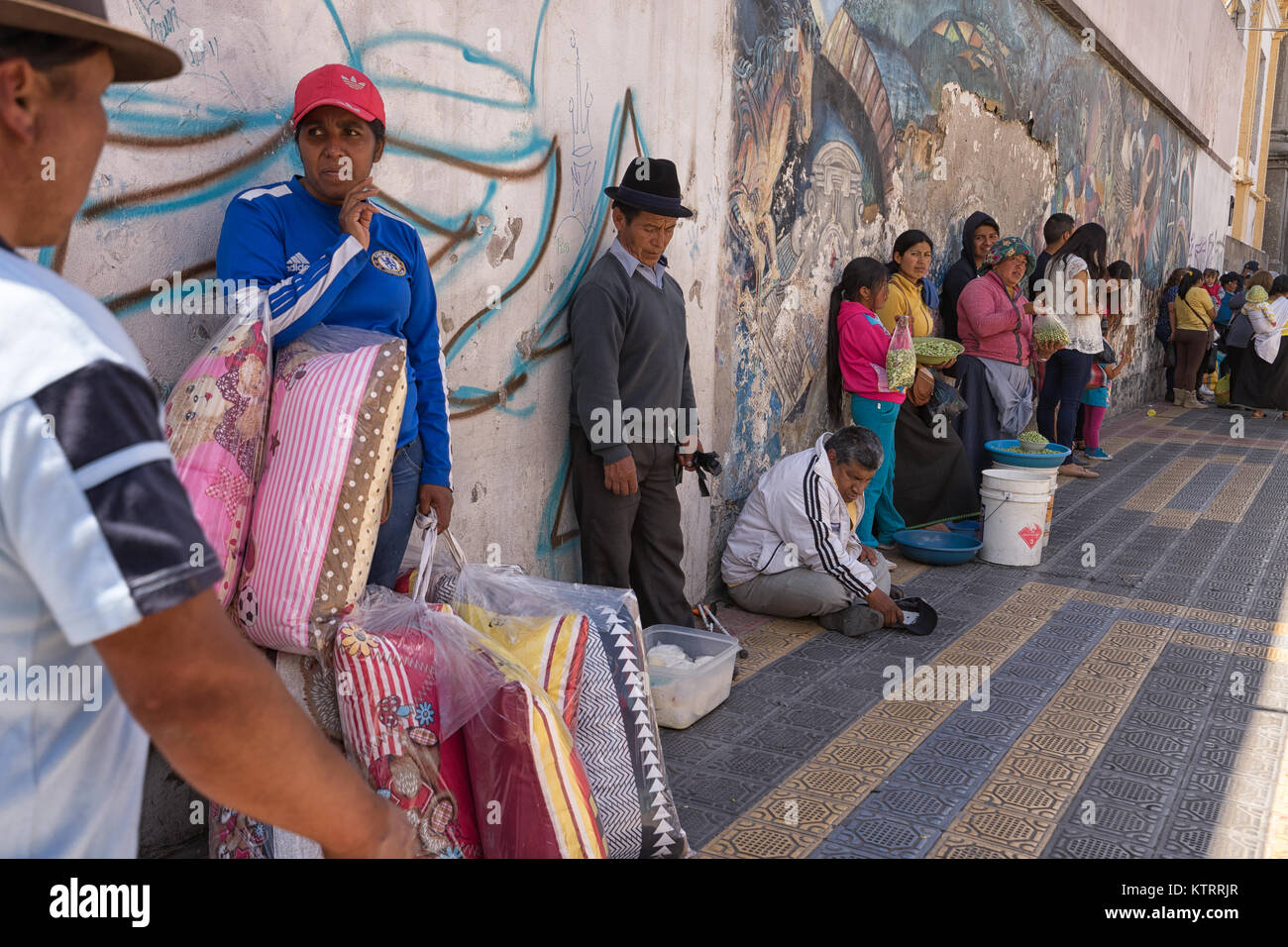 Otavalo, Ecuador-December 23, 2017:people cooling down in the shade on a hot day - Stock Image