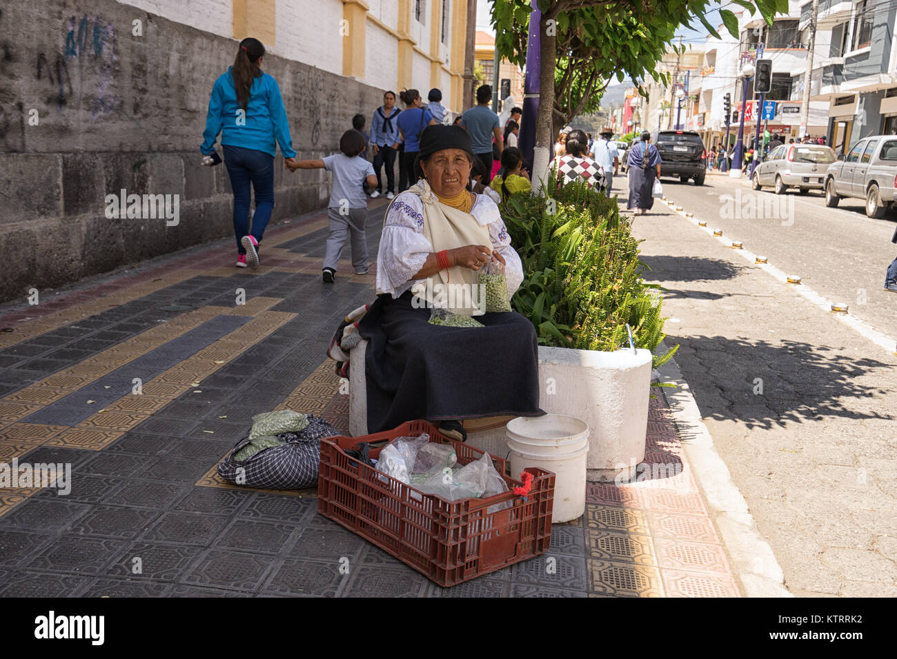 Otavalo, Ecuador-December 23, 2017: ndigenous woman selling peas on the street - Stock Image