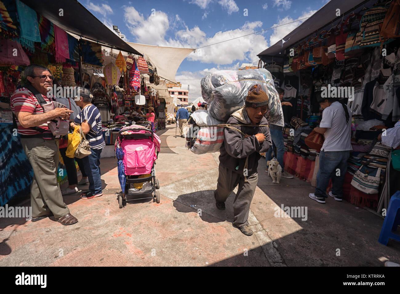 Otavalo, Ecuador-December 23, 2017: local man hauling merchandise through the artisan market on his back - Stock Image