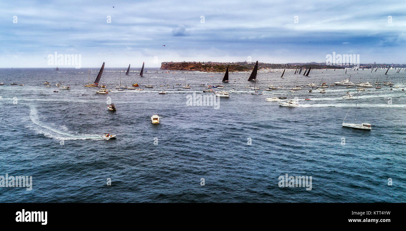 Leaders of Sydney Hobart yacht race clearing from Sydney harbour turning at South Head surrounded by tourists and - Stock Image