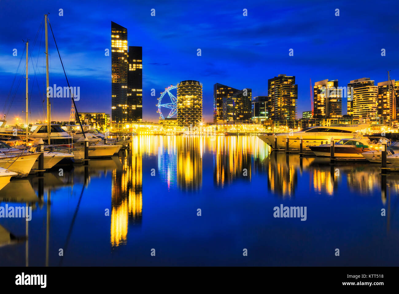 Dark colourful sunset over Docklands suburb in Melbourne on waterfront of Yarra river with marina for yachts. Bright - Stock Image