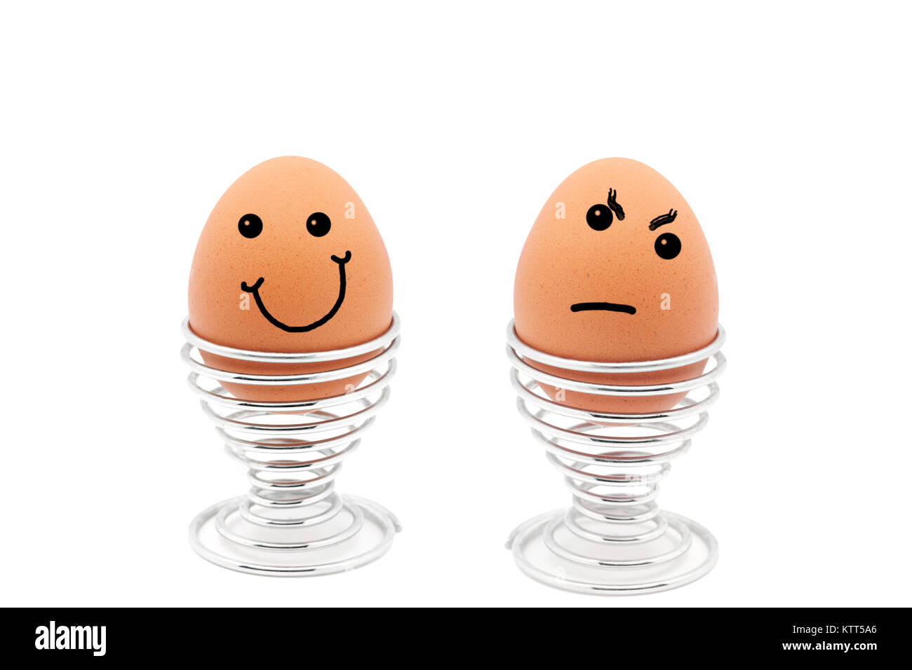 Two eggs in egg cups with happy and sad faces - Stock Image