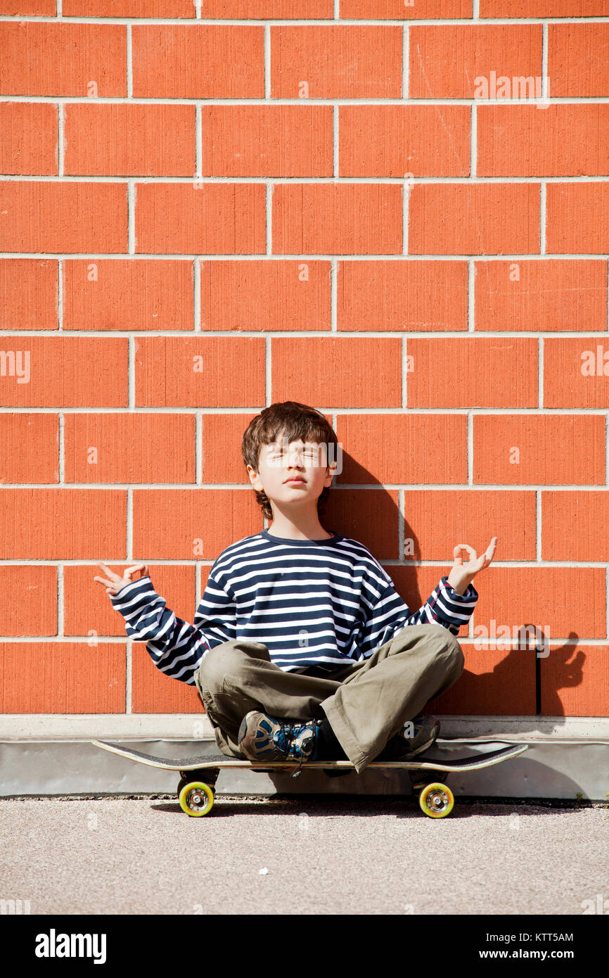 Young boy sitting on his skateboard table. he meditates by praying kindness, peace and love - Stock Image