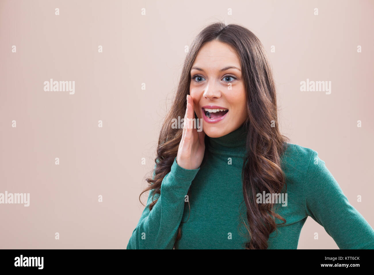 Portrait of young happy woman who is calling to someone - Stock Image