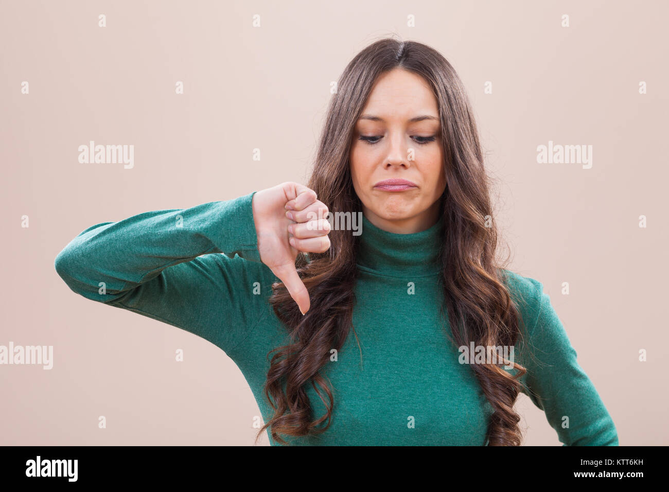 Portrait of displeased women who is showing thumb down - Stock Image