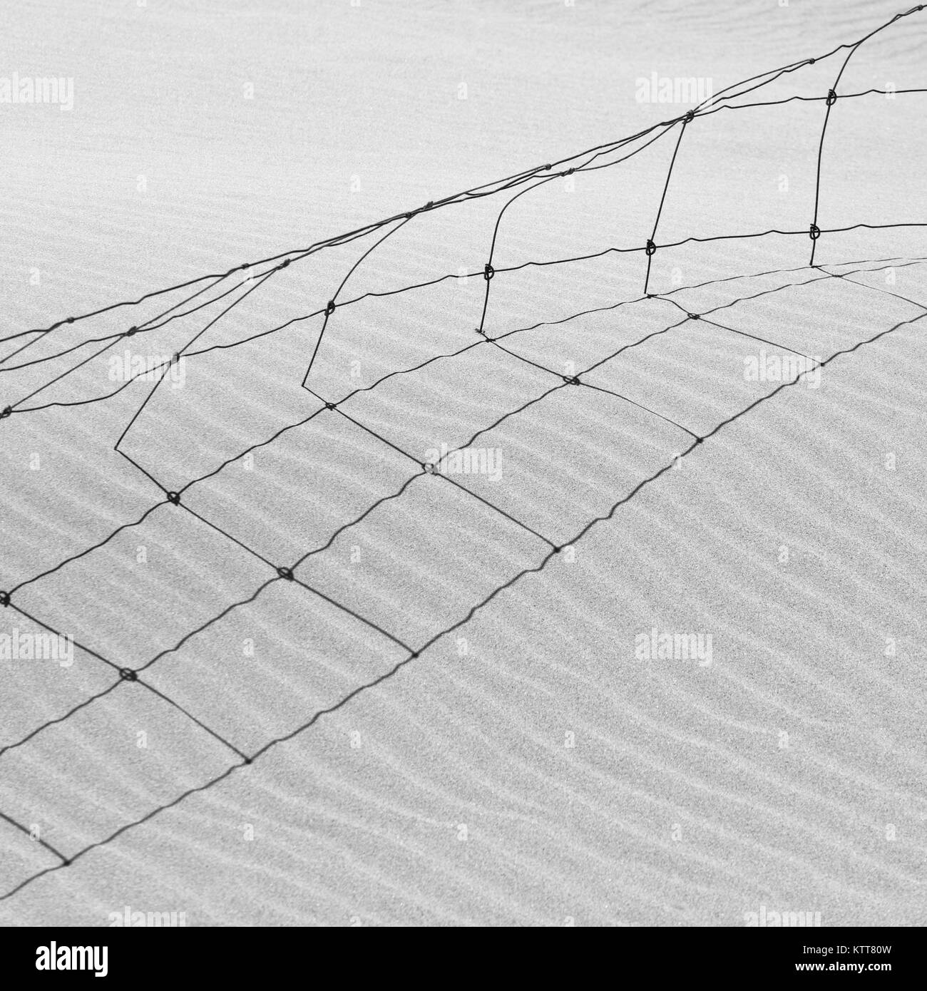 Abstract wire fence in sand dune Black and White sorrento beach Perth - Stock Image