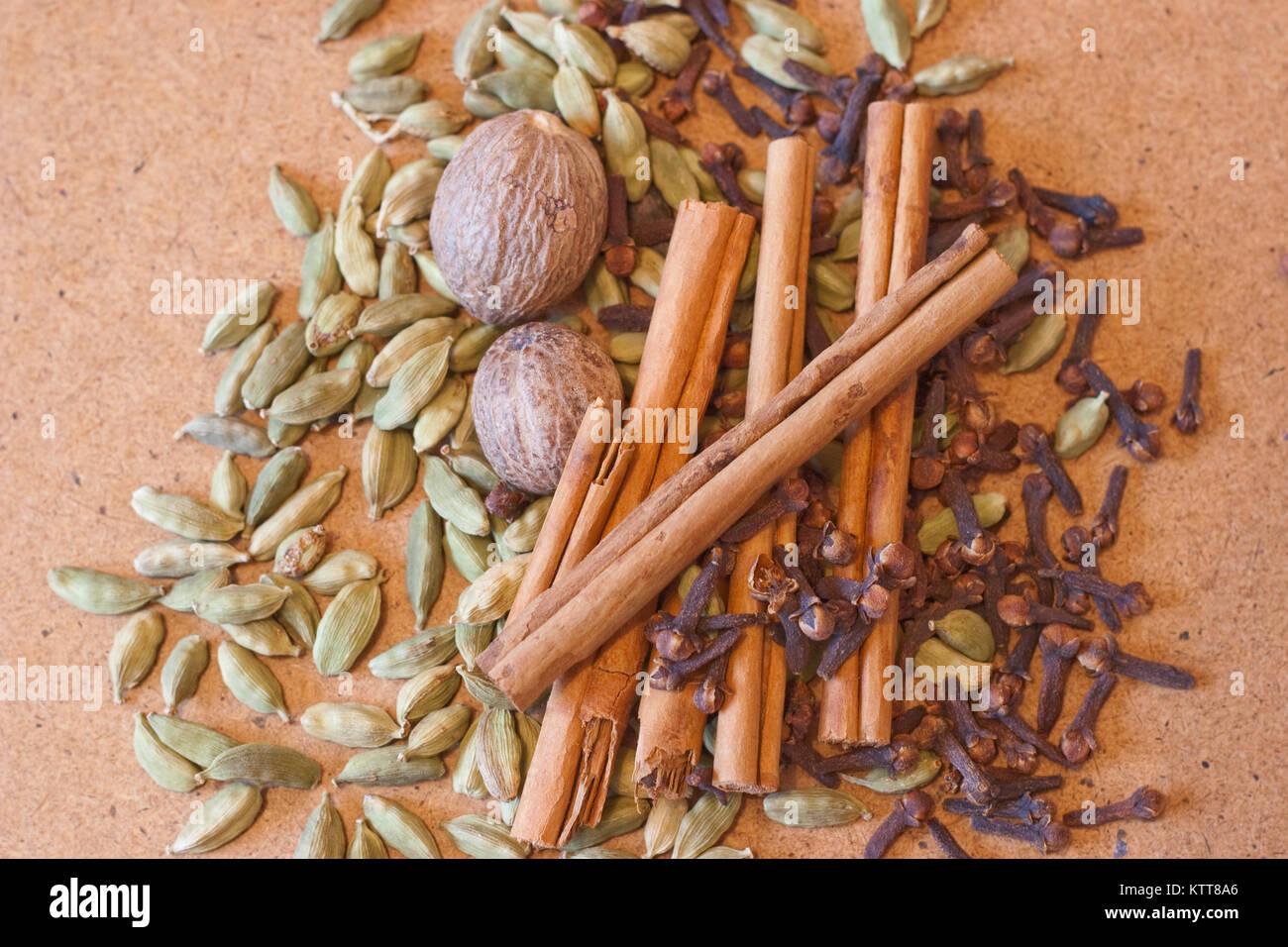 Cardamom pods, cinnamon sticks, whole nutmeg and cloves on plain background - Stock Image