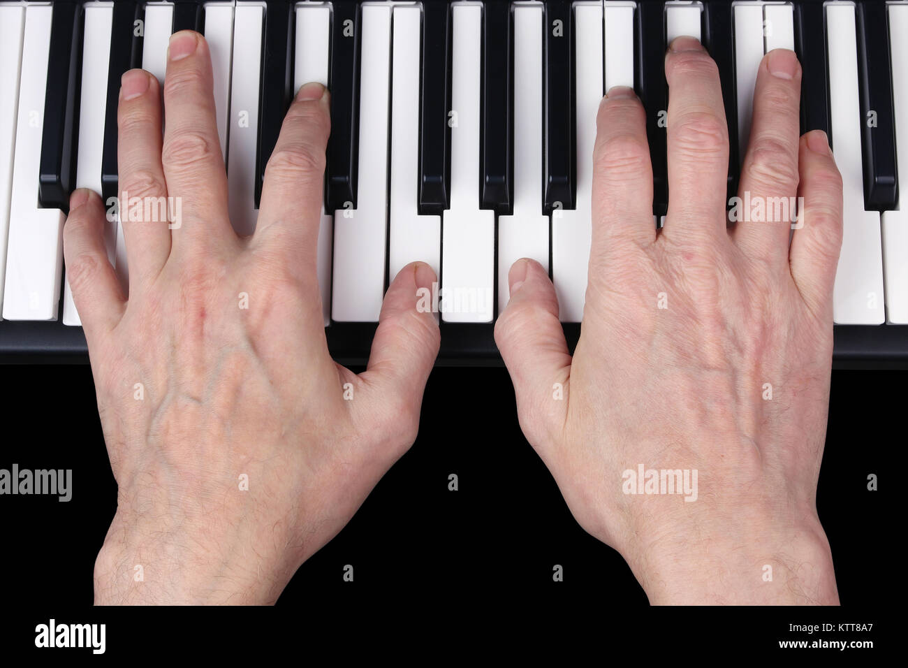 An elderly retired man plays an old melody on the keyboard of the synthesizer. Studio human eyes view  shot. Partially - Stock Image