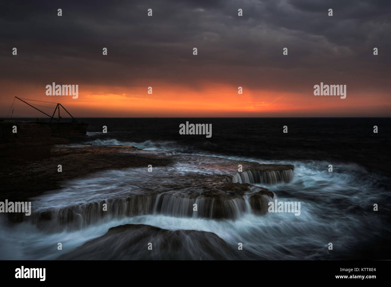 Red Crane and Stormy Sea Nightscape - Stock Image