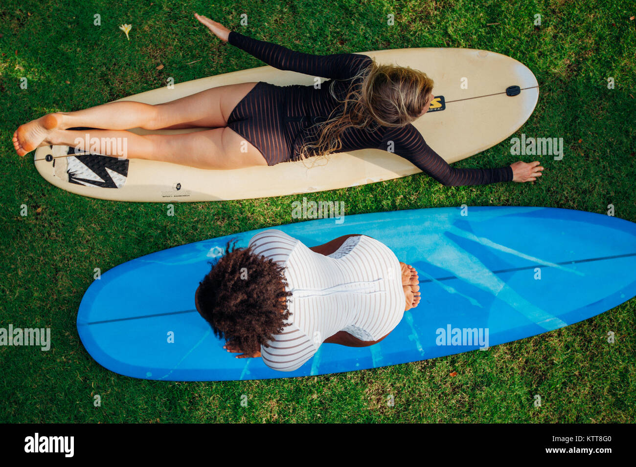Mixed race surfer girls having fun with surfboards - Stock Image