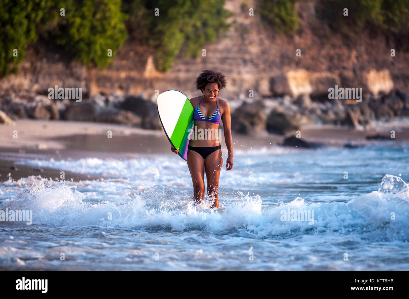 Surfer girl with afro hairstyle walking with surfboard on the Padang Padang beach at sunset in Bali, Indonesia - Stock Image