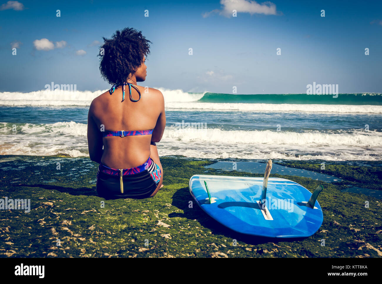 Surfer girl with afro hairstyle sitting next to blue surfboard on the green coral reef in front of a breathtaking - Stock Image