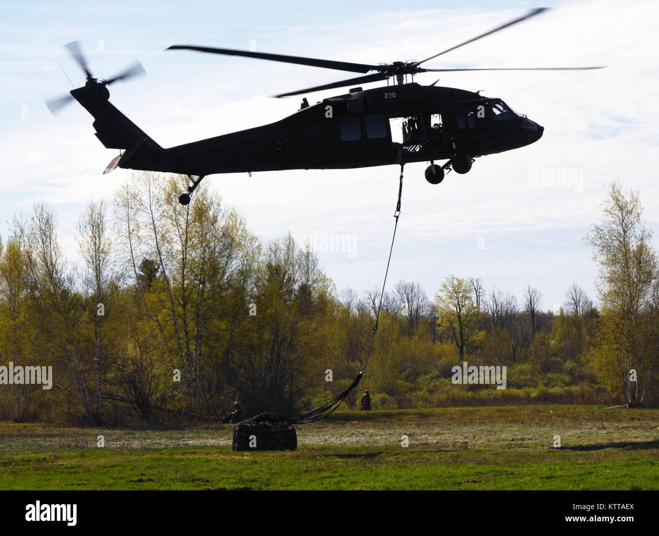 An aircrew of the New York Army National Guard's 3rd Battalion, 142nd Aviation airlifts 105 mm howitzer ammunition - Stock Image