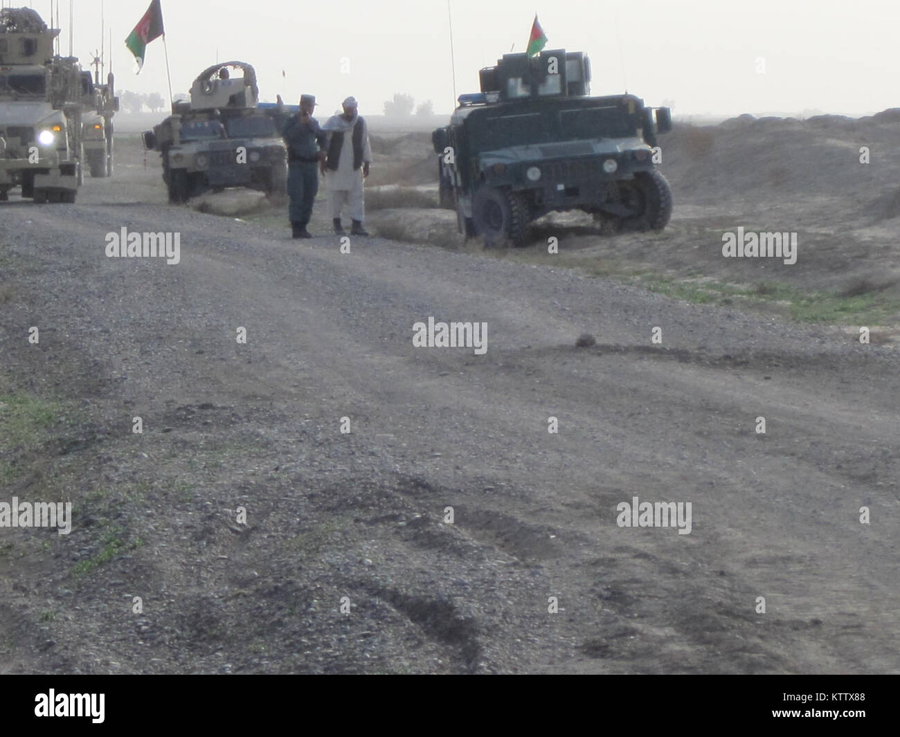 A convoy of American Soldiers, Afghan Soldiers and Afghan National Police (ANP) halt after discovering an IED buried Stock Photo