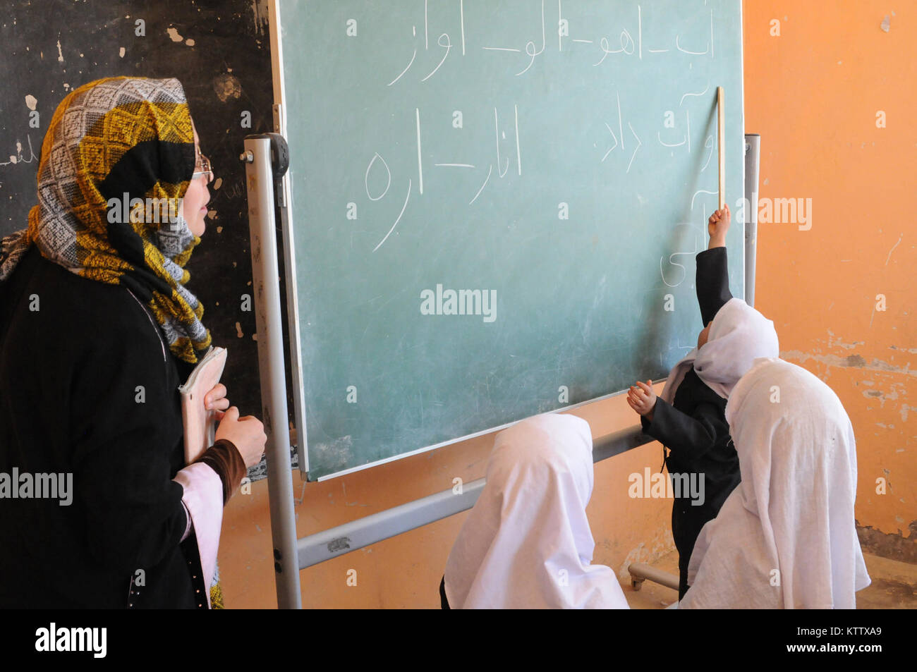 A young Afghan girl points out a word to her teacher at the Aliabad School near Mazar-e-Sharif, Balkh Province, Stock Photo