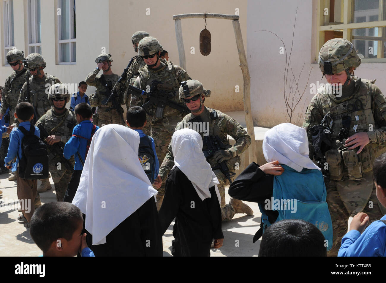 Soldiers of the 37th Infantry Brigade Combat Team shake hands with students as they leave the Aliabad School near - Stock Image
