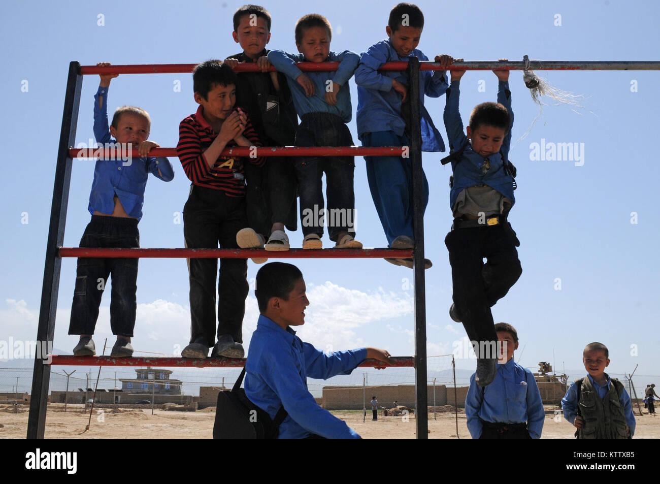 Young Afghan schoolboys play on the Aliabad School's jungle gym near Mazar-e-Sharif, Balkh Province, Afghanistan, - Stock Image