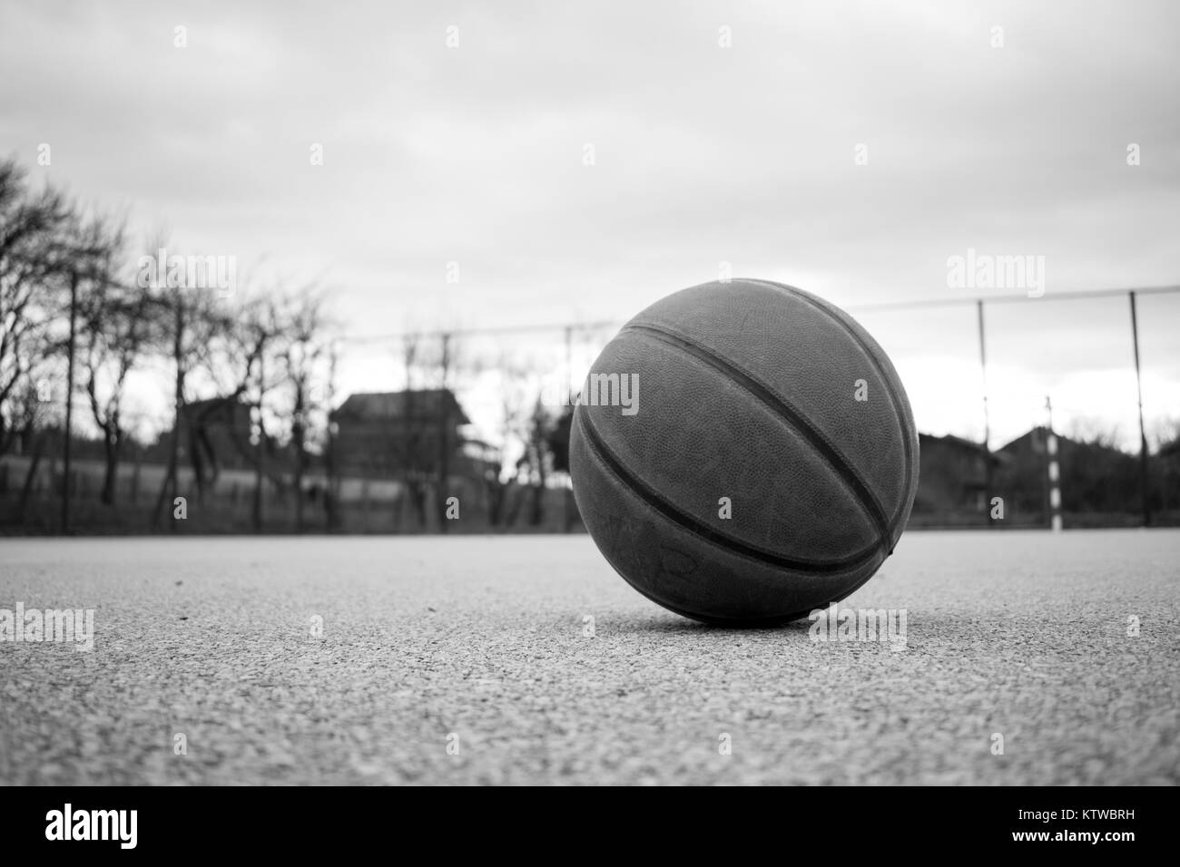 Black and white image of used orange basketball with basket in background basketball street court