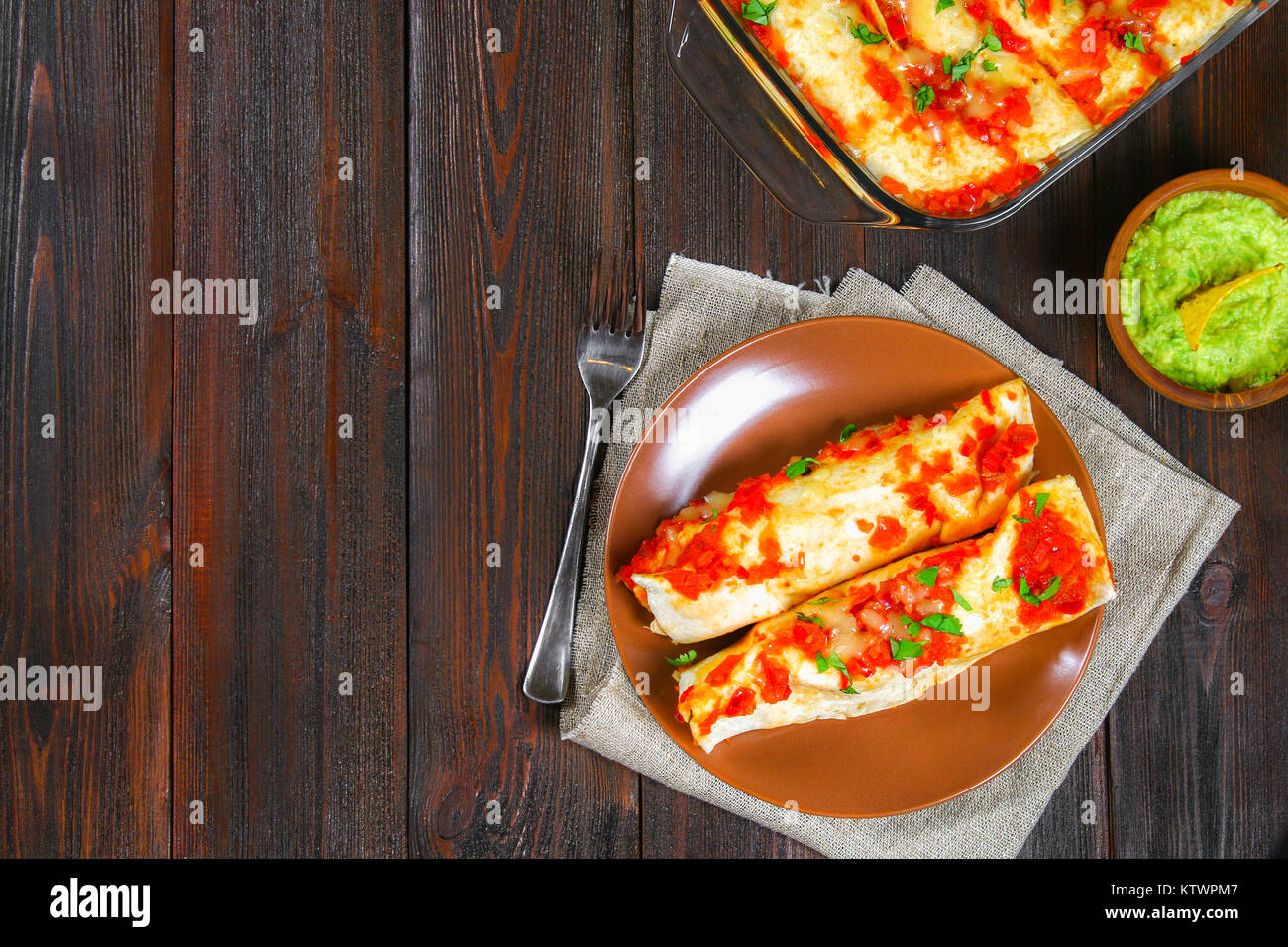 Homemade chicken enchiladas in dish on wooden table. Top view Stock Photo