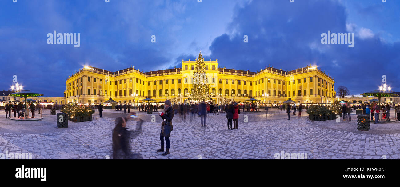 Panormaic view of illuminated Schönbrunn palace in Christmas time with fairy lights decorated Christmas tree and market at blue hour dusk in Advent. Stock Photo