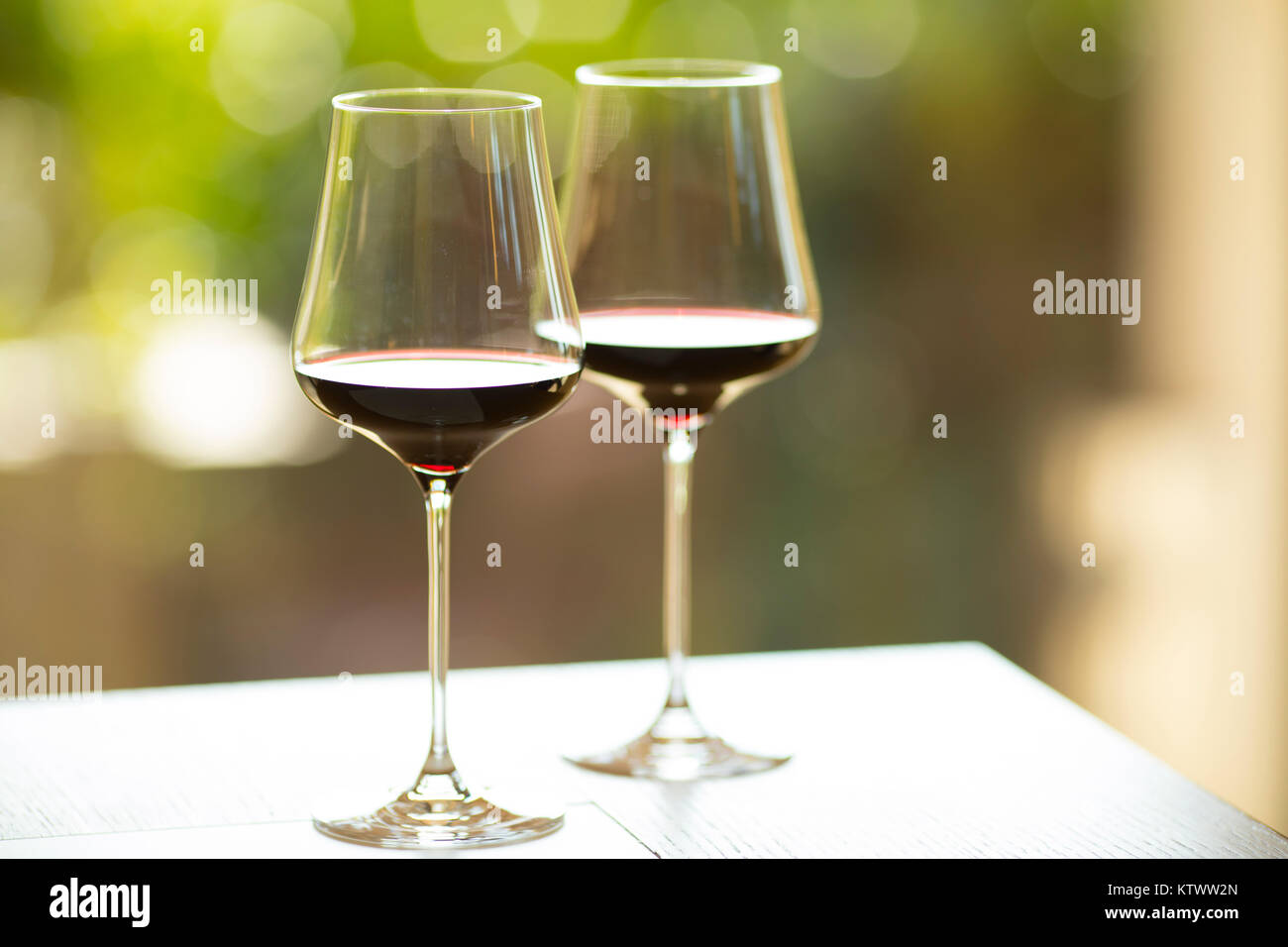 Closeup of two red wine glasses with a colorful, sunny atmosphere. Summer ambience, low depth of field - Stock Image