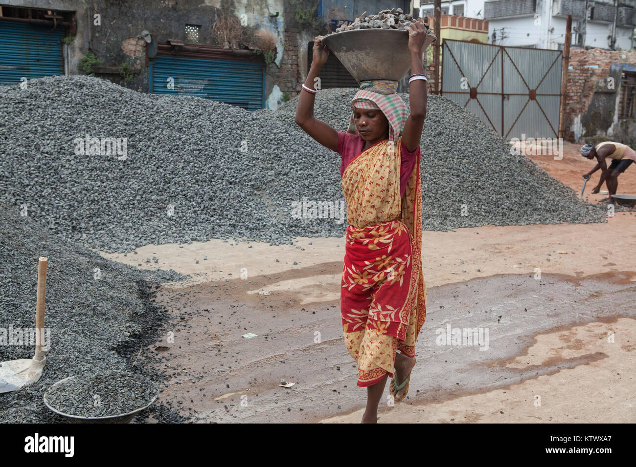 A female labourer carries a tray of stone chippings through a building site in Asansol, India Stock Photo