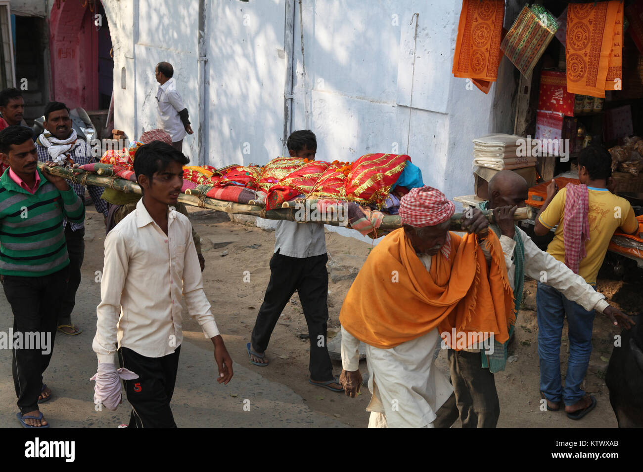 The shrouded body of a deceased man is carried on a stretcher through the streets of Gaya to the cremation site - Stock Image