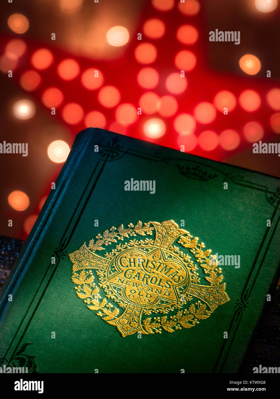 Christmas Carols 'New and Old' music book cover with warm inviting festive Christmas lights behind - Stock Image