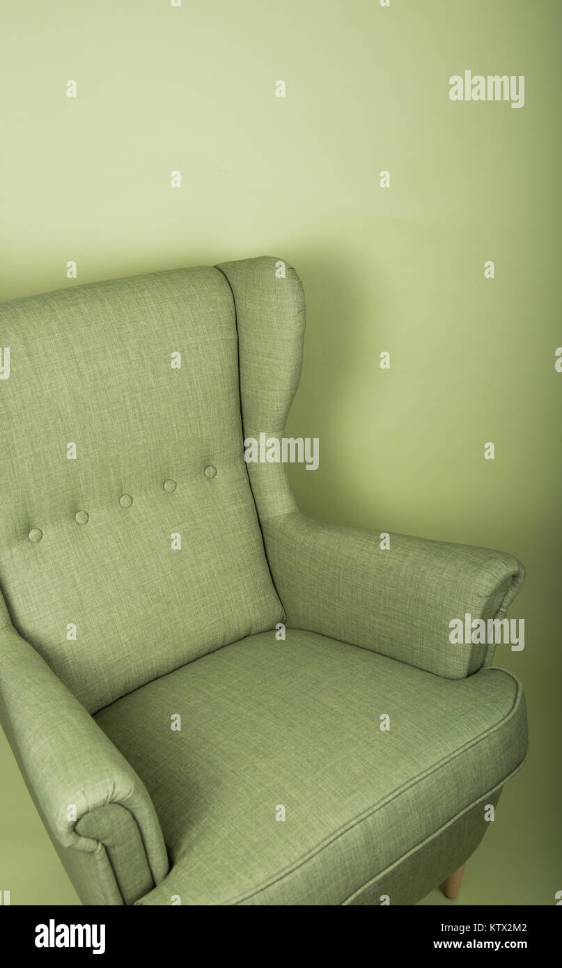 Green Upholstered Arm Chair next to Similar Colored Wall - Stock Image