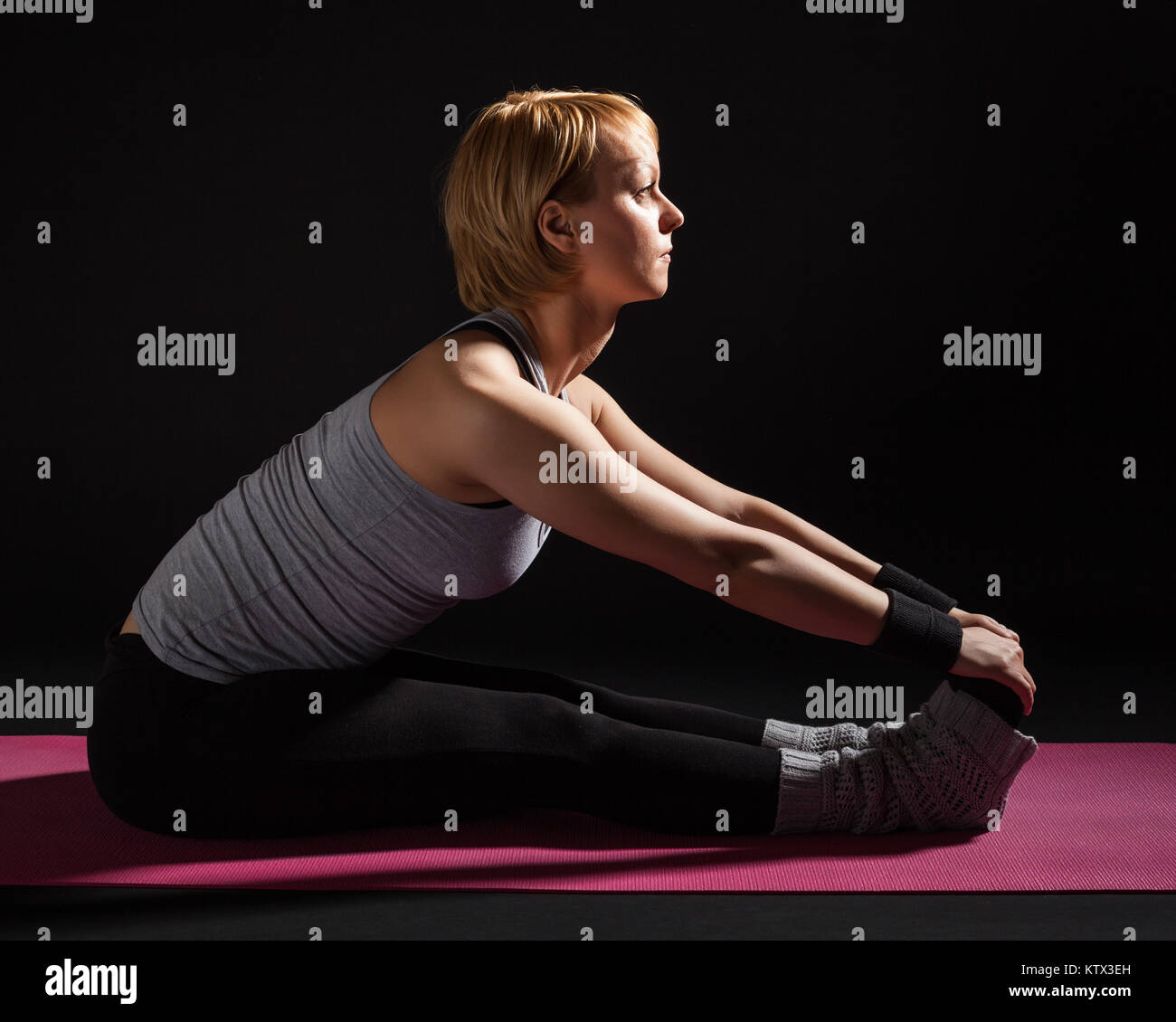 Young woman practicing yoga,  Paschimottanasana / Seated Forward Bend pose - Stock Image