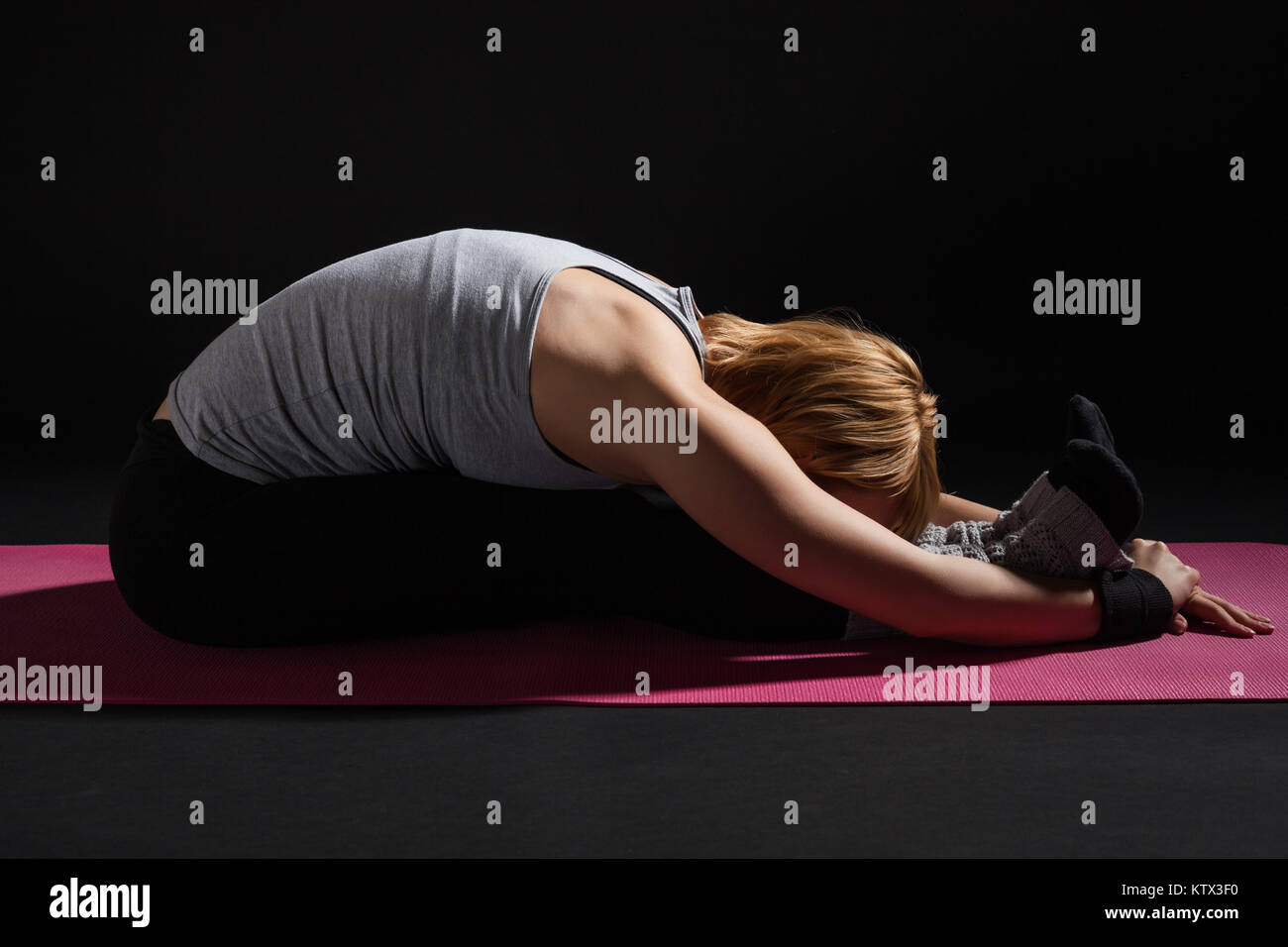 Young woman practicing yoga, Paschimottanasana / variation of Seated Forward Bend pose - Stock Image