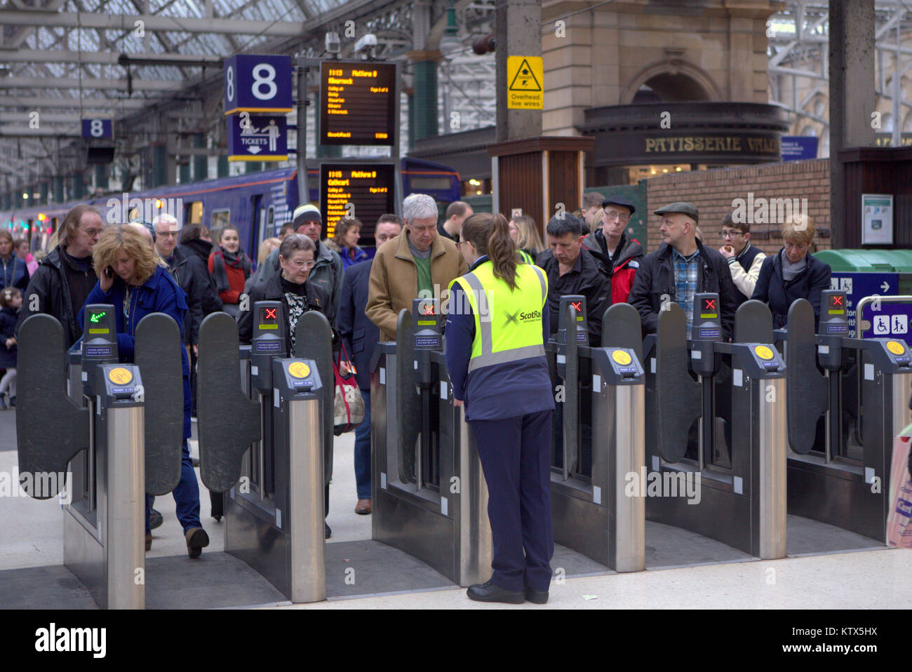 Glasgow central railway station ticket turnstiles during rush hour with queues and train staff  collecting tickets - Stock Image