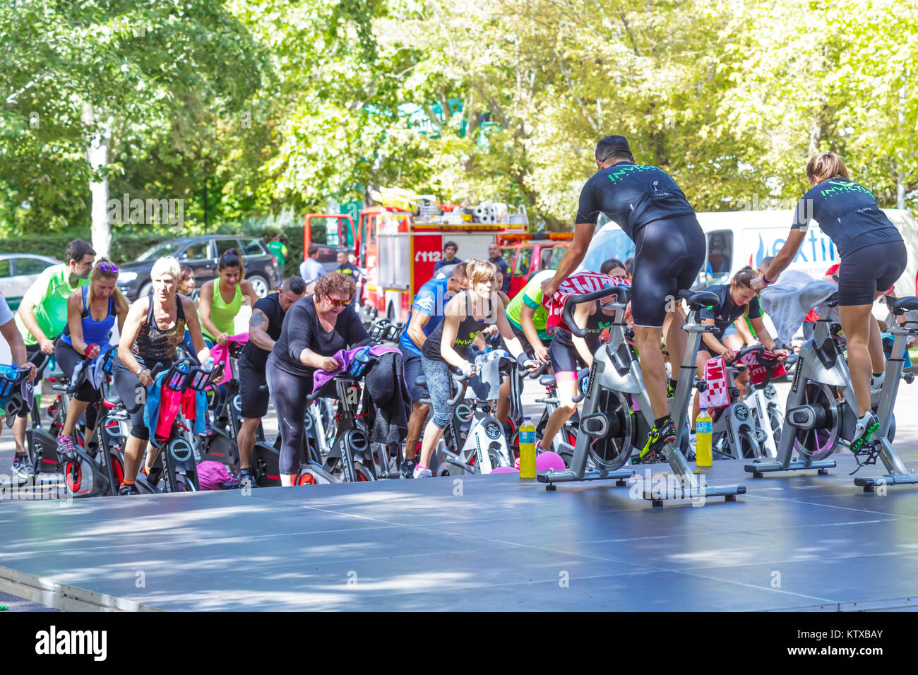 Zamora, Spain - September 02, 2017: People perform a spinning session outdoors in an urban park. Cycle Against Cancer. Stock Photo
