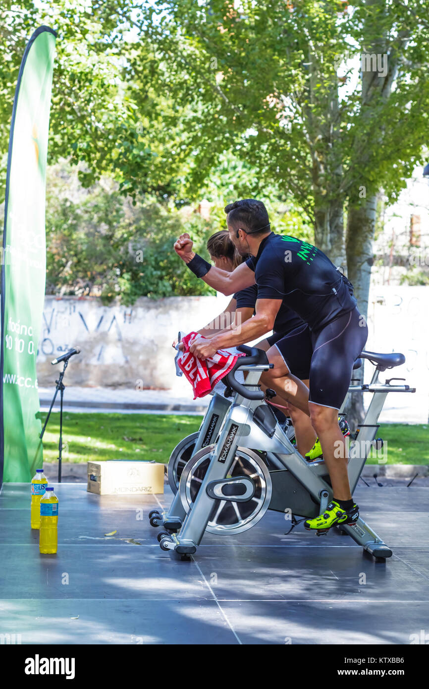 Zamora, Spain - September 02, 2017: Coaches cheering spinning session outdoors in an urban park. Cycle Against Cancer. Stock Photo