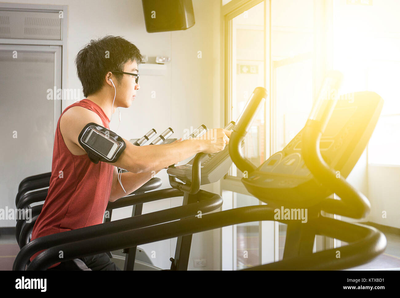 Handsome man on running machine with listen music for relax in gym