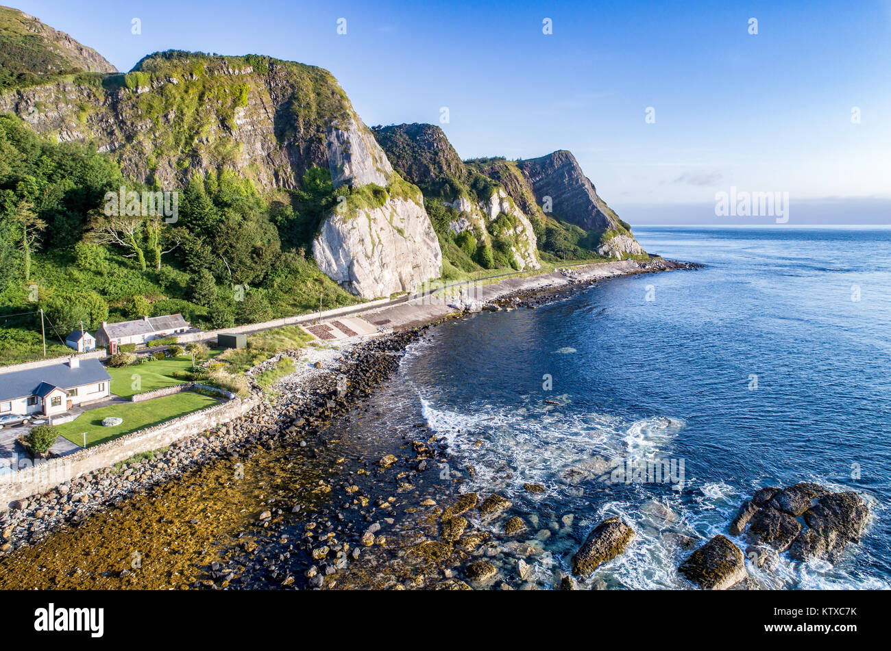 The eastern coast of Northern Ireland with cliffs and Antrim Coastal Road, a.k.a. Causeway Coastal Route. Aerial - Stock Image