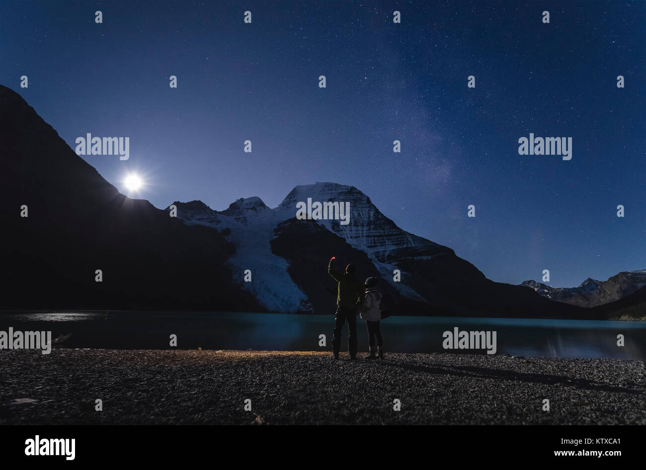Couple watching moonrise over Mount Robson from the Berg Lake in the Mount Robson Provincial Park, UNESCO World - Stock Image