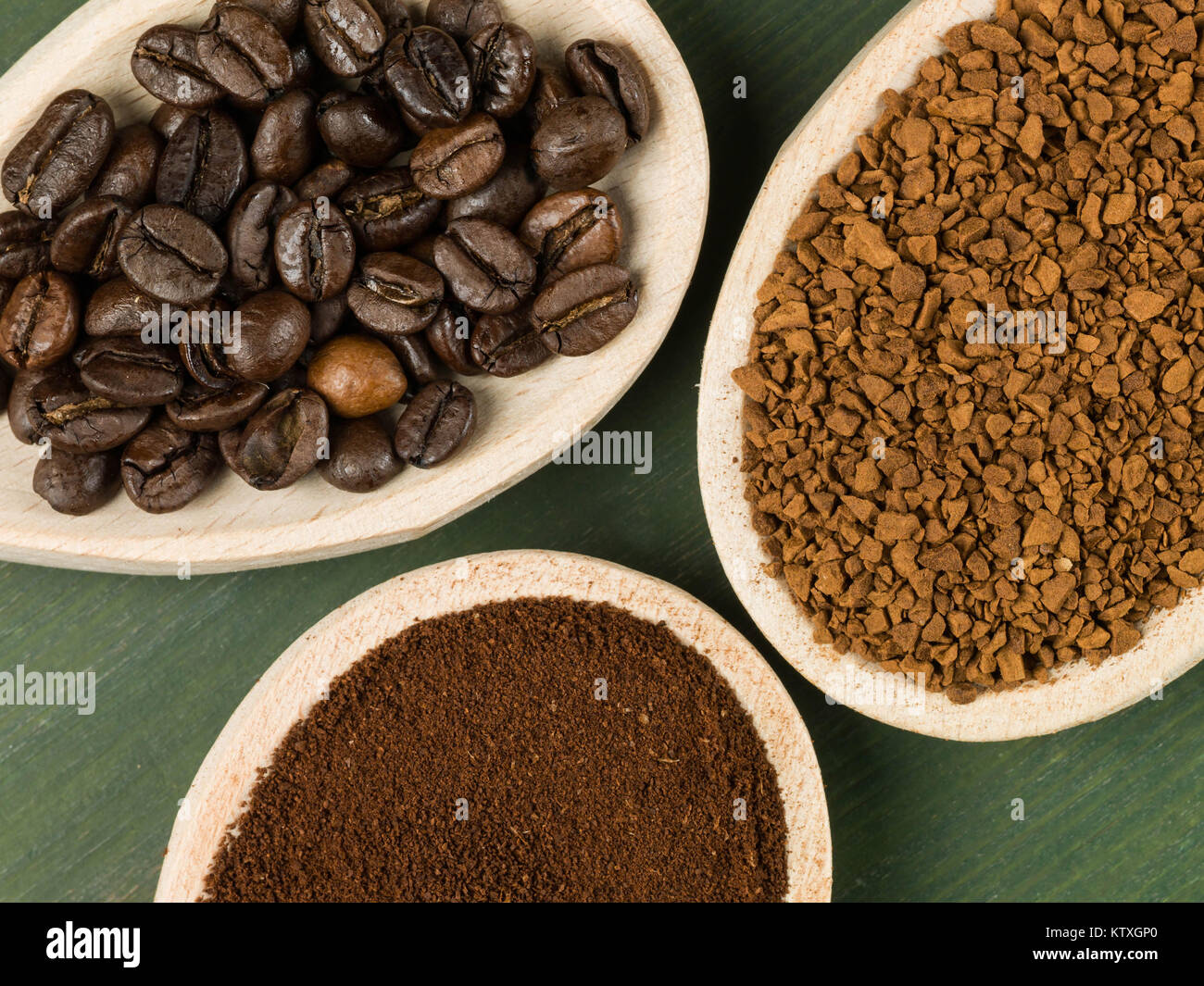 Spoonfuls of Instant Granulated and Roast Coffee Beans Against a Green Background - Stock Image