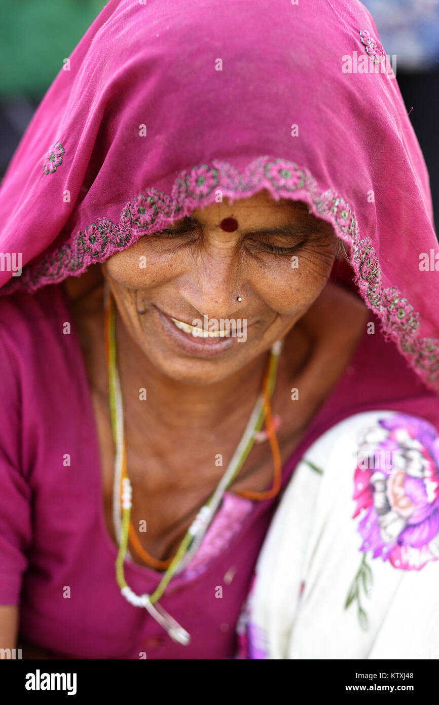 portrait of indian woman in a pink traditional dress with head covered with pink veil, looking down, village near - Stock Image
