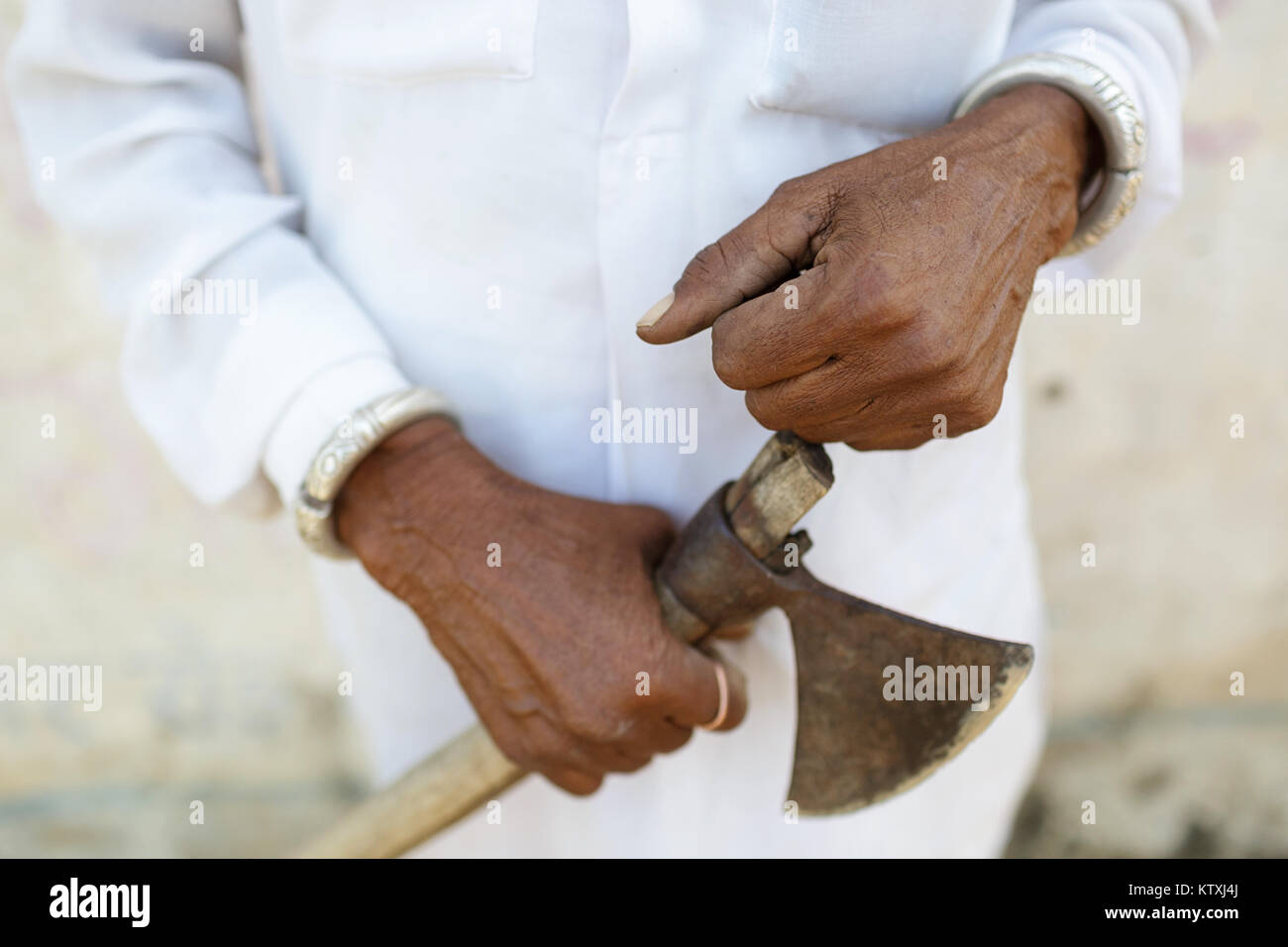 Close-up of hands of old indian man in white outfit holding an axe, in a village near Pushkar, Rajasthan, India. - Stock Image